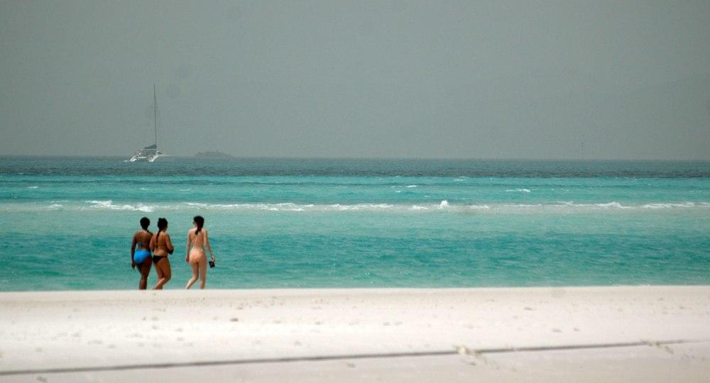 Tres chicas pasean por la Whitehaven beach, en las Whitsunday Islands, considerada una de las mejores playas del mundo.
